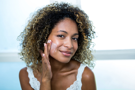 Young woman applying moisturizer in bathroom