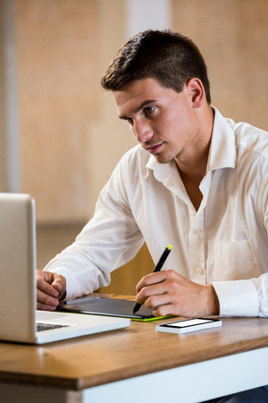graphics tablet: Man working on his graphics tablet in office