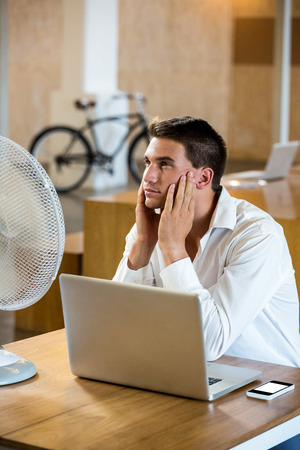 breeze: Man enjoying a breeze with laptop at desk in office