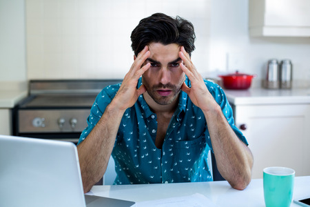 tensed: Tensed man sitting with bills and laptop in kitchen at home