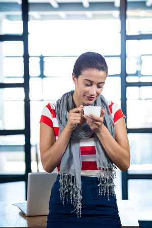 smelling: Beautiful woman smelling a cup of coffee in office