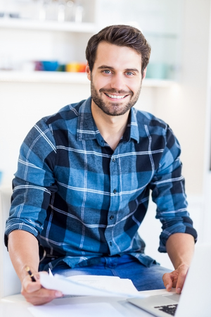 figuring: Portrait of young man paying his bill online with laptop in the kitchen Stock Photo