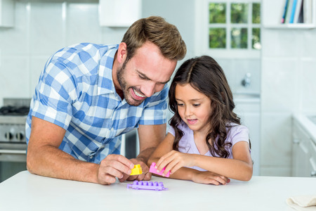 toy block: Happy father and daughter playing with toy block at table in kitchen