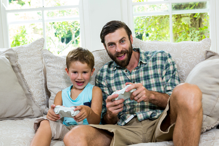playing video game: Portrait of father and son playing video game on sofa at home Stock Photo