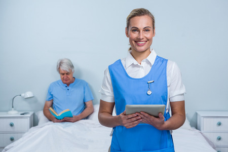 keep an eye on: Portrait of smiling nurse holding digital tablet with senior man in background at hospital