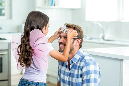 cute angel: Daughter in angel costume putting crown on father head in kitchen