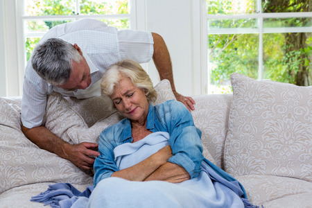 seniors suffering painful illness: Senior man talking to ill wife resting on sofa at home