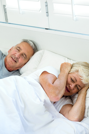 snoring: High angle view of irritated senior woman sleeping by snoring man on bed at home