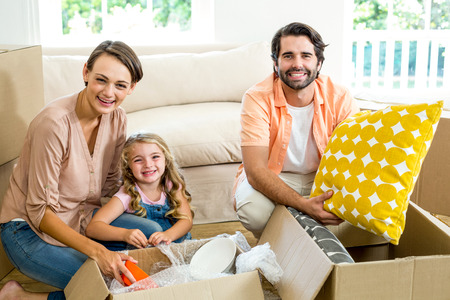 unpacking: Portrait of happy family unpacking boxes in new house Stock Photo