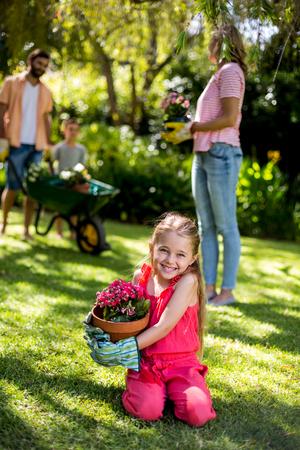 girl holding flower: Smiling girl holding flower pot while family standing in background