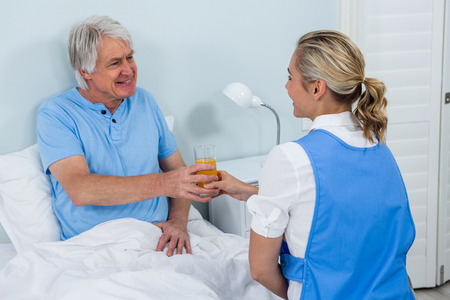 tomando refresco: Nurse giving juice to smiling senior man at home