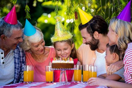 multi generation: Smiling multi- generation family celebrating birthday at yard Stock Photo