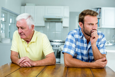 tensed: Close-up of tensed father and son sitting at table in kitchen