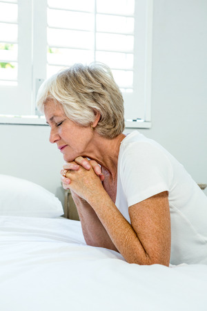 Aged woman praying against window in bedroom at home