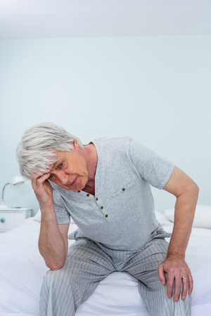 seniors suffering painful illness: Senior man suffering from headache while sitting on bed at home