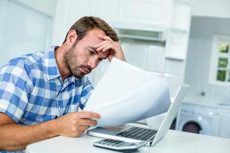 tensed: Tensed man looking in documents while sitting by laptop at table in kitchen Stock Photo