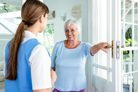 health club: Happy aged woman standing nurse by door at health club Stock Photo
