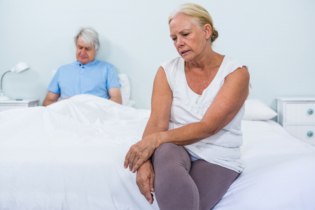 dreariness: Sad senior couple sitting in bedroom at home