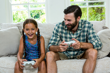 playing video game: Happy father looking at daughter while playing video game on sofa at home