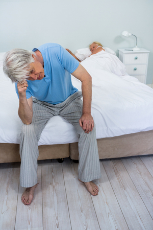 seniors suffering painful illness: Tensed senior man touching head while woman sleeping on bed at home