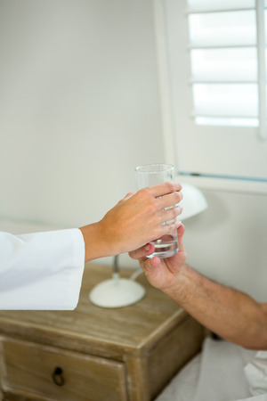 doctor giving glass: Cropped image of doctor giving glass of water to senior patient at home