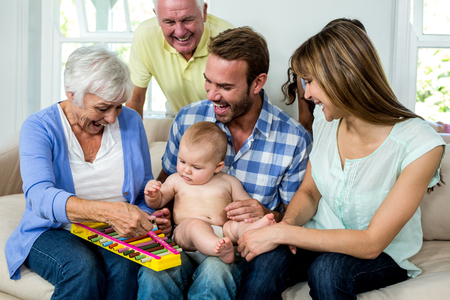 multigeneration: Happy multi-generation family showing xylophone to baby boy on sofa Stock Photo