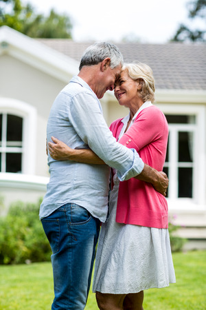 arms around: Happy senior couple standing with arms around outside house in yard