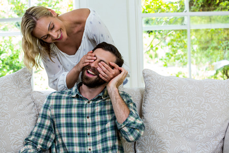 eyes closing: Cheerful wife closing husband eyes from behind against window at home
