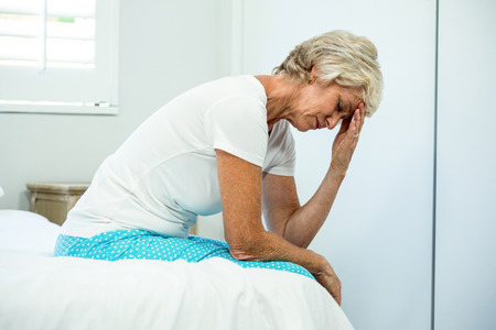mujer sentada: mujer de mediana edad se tensó con los ojos cerrados sentado en la cama en su casa