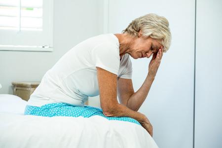 Verspannte gealterte Frau, mit Augen zu Hause geschlossen sitzt auf dem Bett
