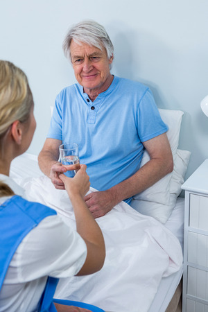keep watch over: Nurse giving water and  medicins to senior man at home Stock Photo