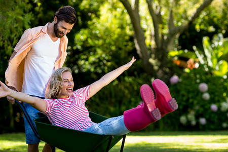 couple nature: High angle view of man pushing woman sitting in wheelbarrow at yard Stock Photo