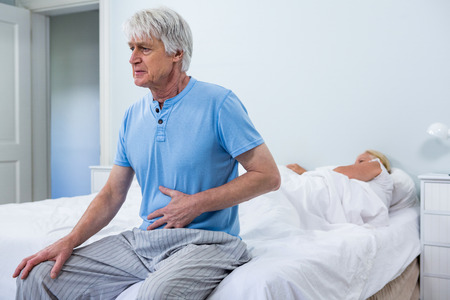 seniors suffering painful illness: Senior man having stomach pain while sitting on bed at home