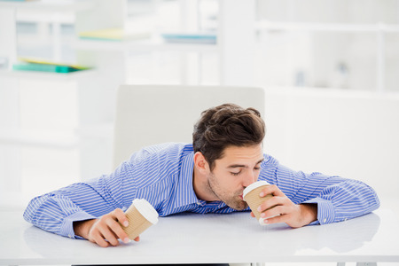 disposable cup: Businessman having coffee from disposable cup in office
