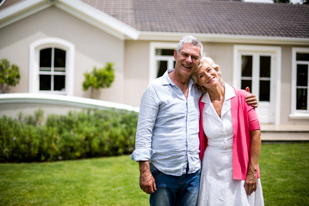 arms around: Smiling senior couple with arms around standing outside house in yard