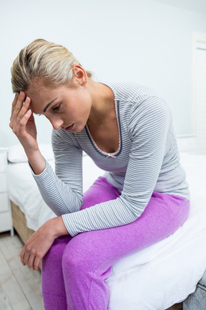 dreariness: Young woman with headache sitting on bed at home