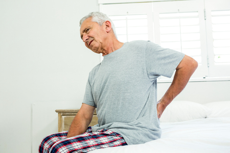 seniors suffering painful illness: Senior man suffering from backache against window on bed at home