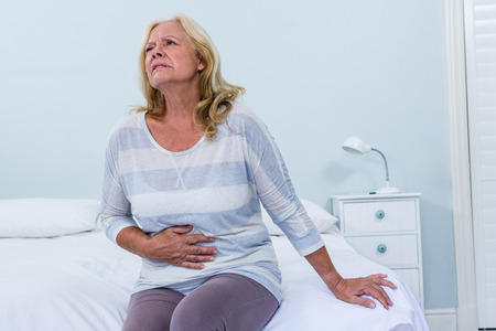 seniors suffering painful illness: Senior woman sitting on her bed has stomach ache in bedroom