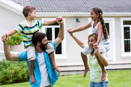 shoulder carrying: Parents carrying children on shoulder enjoying in yard Stock Photo