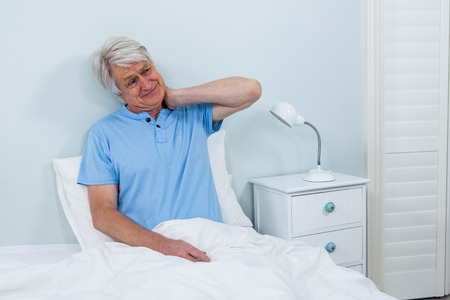 senior man on a neck pain: Senior man suffering from neck pain while sitting on bed at home