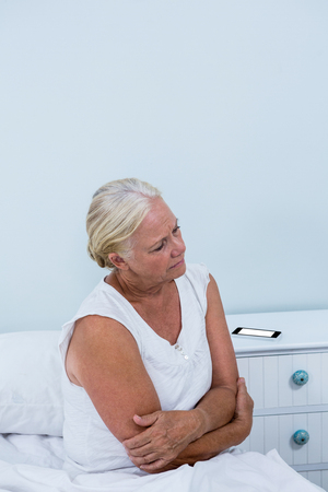 seniors suffering painful illness: Senior woman having stomach pain while sitting on bed at home