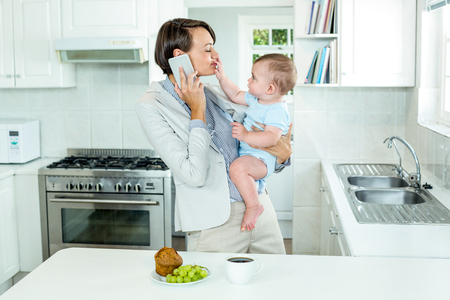 multi family house: Businesswoman talking on cellphone while playing with son by kitchen table Stock Photo