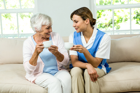 care at home: Smiling nurse and senior woman holding coffee cups on sofa at home Stock Photo