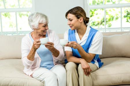 Usmívající se sestra a starší žena drží kávové šálky na pohovce doma