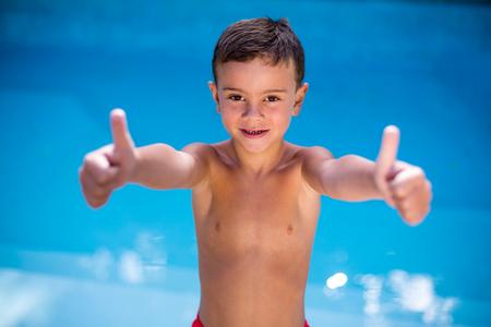 niño sin camisa: Retrato de muchacho sin camisa haciendo un gesto en la piscina Foto de archivo
