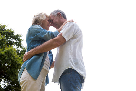 back yard: Romantic senior couple embracing in back yard against clear sky