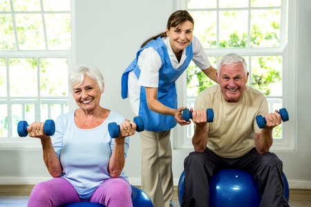 health club: Portrait of smiling nurse assisting senior man and woman at health club Stock Photo