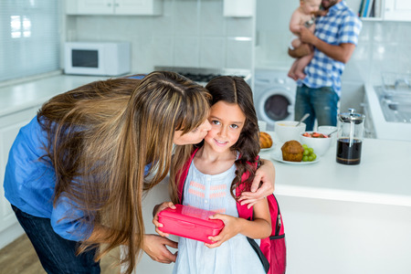 kid school: Mother kissing girl holding school lunch box with family in background at home Stock Photo