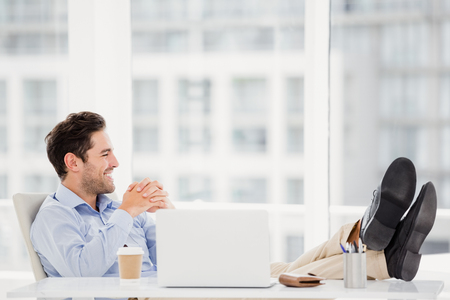 office time: Thoughtful man sitting with feet on table in office