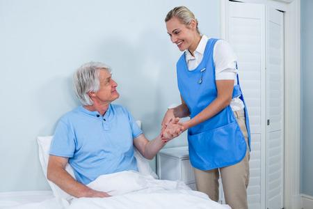 keep watch over: Smiling nurse holding senior man hand in hospital